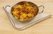 picture of biryani  - Lamb biryani in a balti dish with a serviette on a wooden table top - JPG