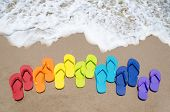 foto of sunny beach  - Color flip flops on sandy beach by the ocean in sunny day - JPG