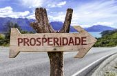 "pic of prosperity sign  - ""Prosperidade"" (In Portuguese: Prosperity) wooden sign with a street background  - JPG"