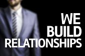 picture of courtesy  - We Build Relationships written on a board with a business man on background - JPG