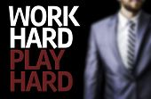 stock photo of hard-on  - Work Hard Play Hard written on a board with a business man on background - JPG