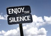 Постер, плакат: Enjoy The Silence sign with clouds and sky background