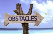 picture of overcoming obstacles  - Obstacles wooden sign with a beach on background - JPG
