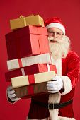 foto of generous  - Generous Santa with pile of giftboxes looking at camera - JPG