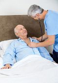 stock photo of male nurses  - Male caretaker checking senior man with stethoscope in bedroom at nursing home - JPG