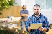 stock photo of coworkers  - Portrait of mid adult manual worker holding digital tablet with coworker standing in background at construction site - JPG