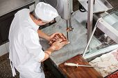 foto of slaughterhouse  - High angle view of butcher cutting meat with bandsaw in butchery - JPG