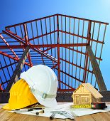 stock photo of model home  - architect working table hard hat house model plan sheet and writing equipment against home roof structure construction site - JPG