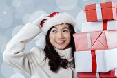 stock photo of scratching head  - Portrait of gorgeous girl scratching her head while wearing santa head and holding christmas gift boxes - JPG