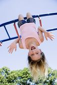 picture of children playing  - Eleven year old girl playing on gym bars in park - JPG