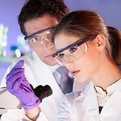 stock photo of microscope slide  - Attractive young scientist and her post doctoral supervisor looking at the microscope slide in the forensic laboratory.