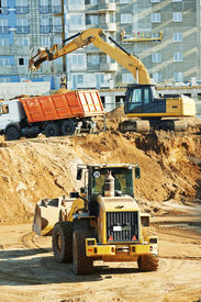 stock photo of boom-truck  - wheel loader and excavator machine loading dumper truck at construction area sand quarry - JPG