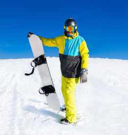 pic of snowboarding  - Snowboarder hold snowboard on top of hill - JPG