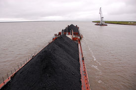 stock photo of coal barge  - Cargo ship with coal at Kolyma river Russia outback Yakutia region - JPG