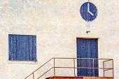 stock photo of windows doors  - Door and window covered with black painted planks on old beige industrial building - JPG