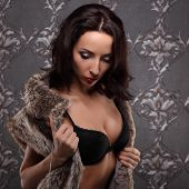 stock photo of seduction  - Sexy brunette woman at black lingerie posing on vintage wall seduction - JPG