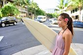 stock photo of hawaiian girl  - Urban surfer Asian girl holding surf board walking in city going surfing in Waikiki beach - JPG