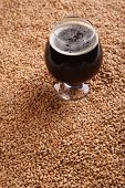 stock photo of malt  - Snifter glass with black stout beer standing over malted barley grains - JPG