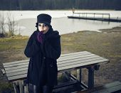 picture of cold-weather  - Fearful fashion woman wearing a winter coat and hat and she posing in a wintry beach cold rainy weather cross processed image - JPG
