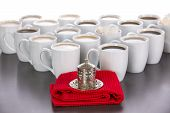 stock photo of latte coffee  - King of the coffee concept with a small cup of Turkish coffee in a traditional metal covered cup standing on a red cloth in front of a triangle of full white ceramic cups of black and latte coffee - JPG