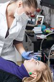 stock photo of eyebrows  - Cosmetologist checking permanent make up on eyebrows - JPG