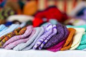pic of thrift store  - a row of multicolored hand-knitted baby socks