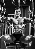 foto of pectorals  - very brawny guy bodybuilder execute exercise on gym apparatus Butterfly Machine in gym - JPG