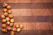 stock photo of hazelnut  - Wooden  surface  with hazelnuts and copy space - JPG