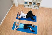 foto of crunch  - High Angle View Of Young Couple Doing Crunches On Exercising Mat - JPG