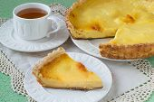 image of custard  - Homemade pie with cheese and custard slice on a plate cup of tea a napkin with lace on a green background - JPG