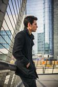 pic of skyscrapers  - Profile of Stylish Young Handsome Man in Black Coat Standing in City Center Street with Skyscraper Behind Him Looking to the Right of the Frame - JPG