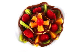 stock photo of crown green bowls  - exotic fruits in chocolate cream on white bowl - JPG