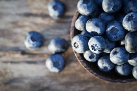 foto of food plant  - Fresh sweet tasty blueberries on a wooden background - JPG