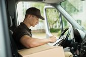 foto of moving van  - Young Delivery Man Checking List On Clipboard In Van - JPG