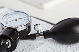 stock photo of manometer  - Medical manometer lying on cardiogram chart closeup - JPG