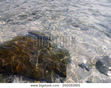 poster of Sea Stones In The Sea Water. Pebbles Under Water. The View From The Top. Nautical Background. Clean