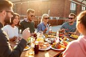 leisure and people concept - happy friends having dinner or barbecue party and eating on rooftop in  poster