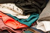 Clothing Scattered Close-up. Lots Of Clothes In Lay On The Table. Background Clothes. Colored Fabric poster