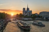 Notre Dame De Paris Cathedral With Cruise Ship In Seine River In Paris, France. Beautiful Sunset In  poster