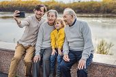 Senior Couple With With Grandson And Great-grandson Take A Selfie In The Autumn Park. Great-grandmot poster
