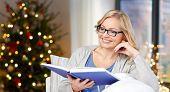 holidays, leisure and vision concept - smiling middle aged woman in glasses reading book over christ poster