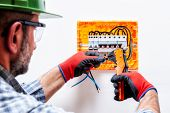 Electrician Technician With Helmet, Goggles And Gloves Protected Hands, Works With Wire Stripper In  poster