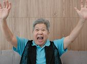 Old Asian Elderly Woman Smiling & Raising Hands With Gladness. Happy Elder Senior Sit On Sofa At Hom poster