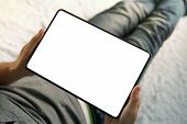 A Lower Half Of A Sitting Man On The Bed Looking Down To The Empty Screen Of An Up-to-date Tablet. A poster