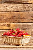 Ripe Delicious Strawberries In Wicker Basket. Basket Full Of Fresh Strawberries On Old Wooden Surfac poster