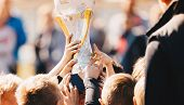 Close-up Of Kids Sports Team With Trophy. Boys Celebrating Sports Achievement. Team Sports Champions poster