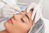 Young Woman Undergoing Procedure Of Permanent Eyebrow Makeup In Tattoo Salon, Closeup poster