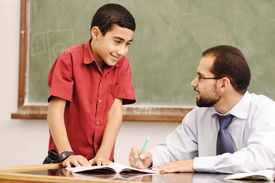 picture of student teacher  - Teacher helping pupil in classroom to resolve schoolwork - JPG
