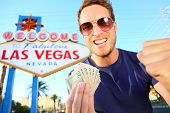 Las Vegas man winning money. Winning gambler standing excited in front of Welcome to Fabulous Las Ve