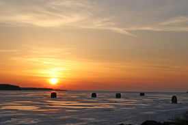 stock photo of ice fishing  - ice fishing shacks out on the frozen harbor at sunset - JPG